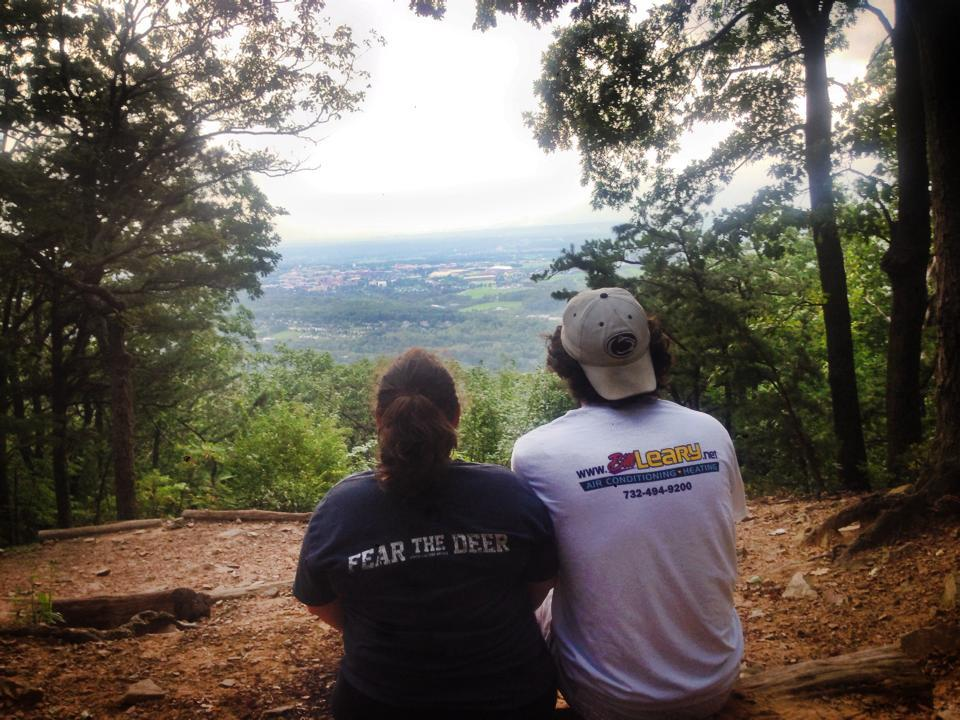 A couple sits closely together and looks down on Happy Valley from an overlook at Mt. Nittany