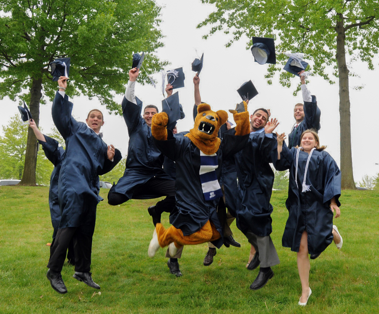 A group of graduating students in caps & gowns jump in the air in front of the Nittany Lion shrine
