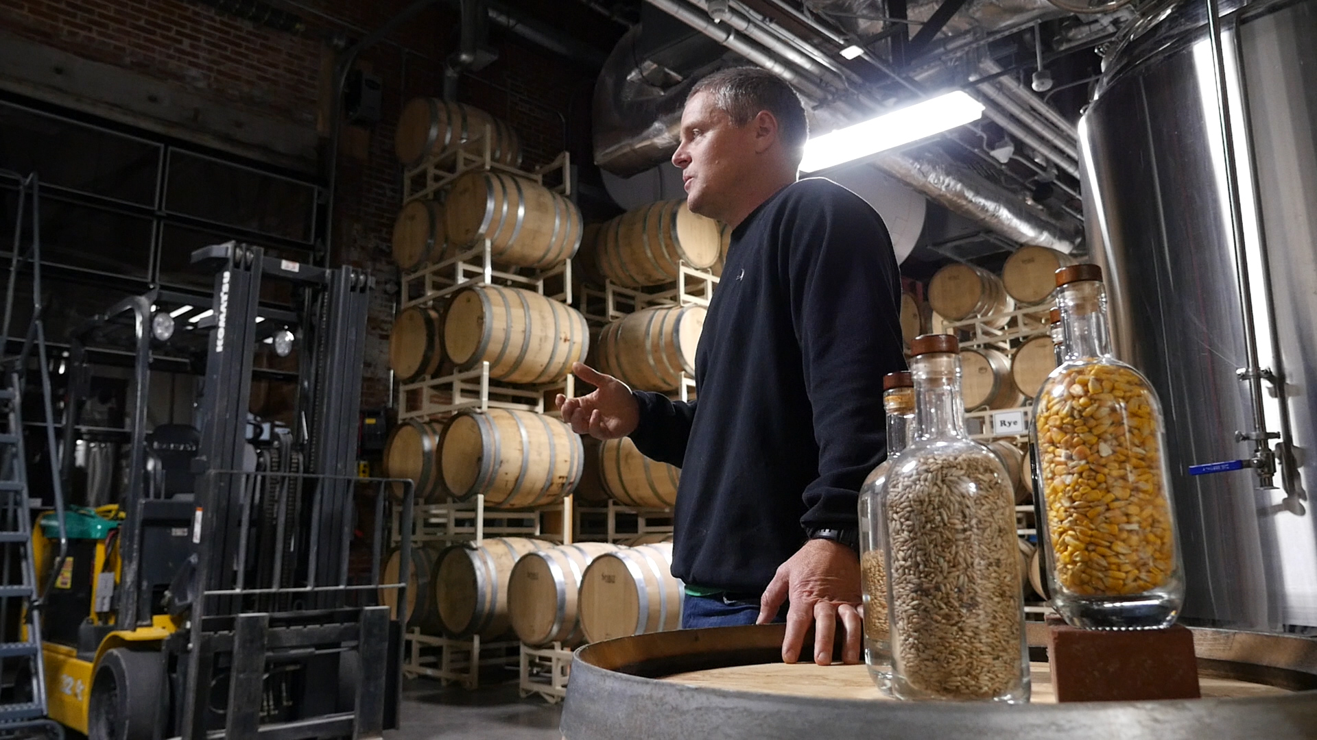 Kevin Lloyd stands in the Big Spring Distillery with grains in the foreground and aging barrels in the background