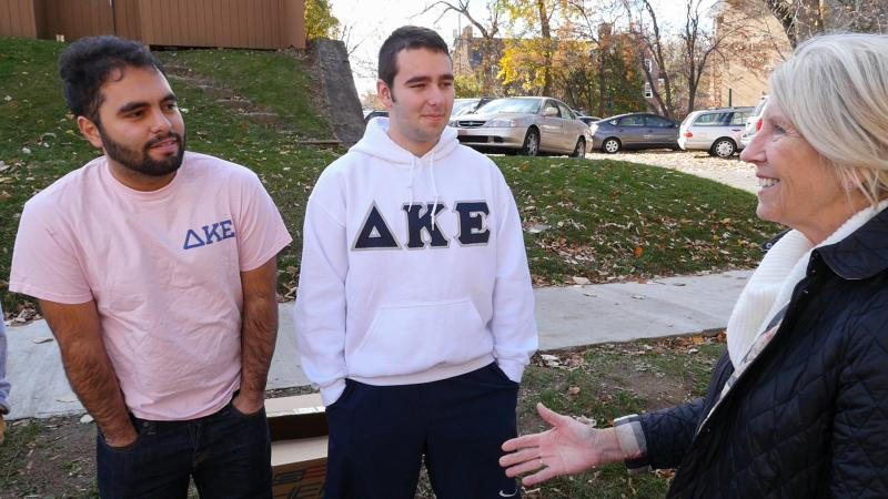 Peg Hambrick extends her hand to greet two fraternity members in her neighborhood
