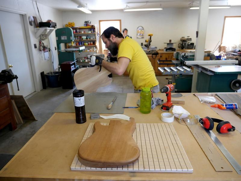 Gary Long shapes a guitar body in his luthiery workshop